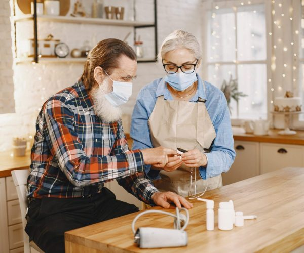 Old couple in a kitchen. Woman in a blue shirt and aprone. People in a medical masks.