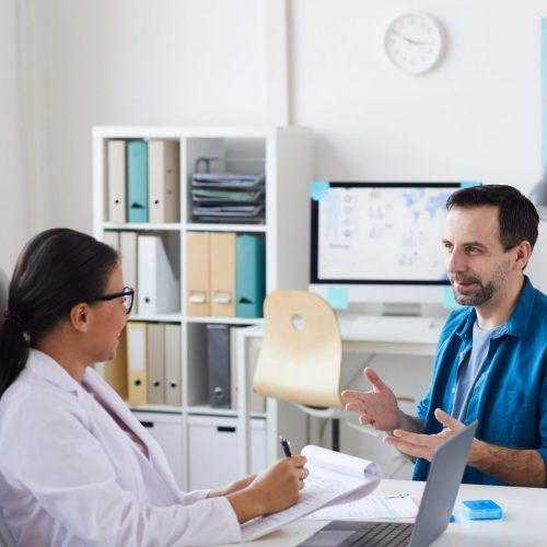 Patient sitting and gesturing at the doctor's office he talking to his doctor during his visit